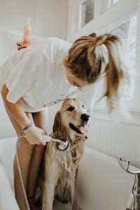 Girl bathing dog in bathtub